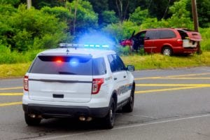Police flashing blue lights at accident damaged car