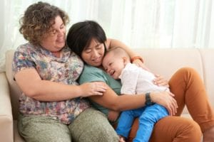 Lesbian couple resting on sofa with their son