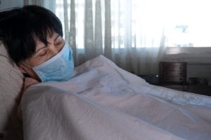 Woman with coronavirus lays down with mask over face