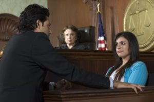 A lawyer questioning a witness in front of a judge in a courtroom